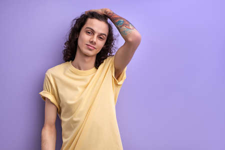 Portrait of young caucasian man touching curly black hair. Handsome male in yellow casual t-shirt posing isolated over purple studio background. People, youth and lifestyle concept. Standard-Bild
