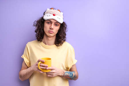 Lazy Student Guy In Casual Wear Need some sleep, dissatisfied male with cup of coffee in the morning, posing isolated over purple background
