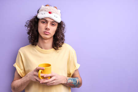 Brunette curly hair caucasian man has no enough sleep, want to go in bed in the morning, dressed casually with eyemask for sleeping, holding yellow mug in hands Standard-Bild