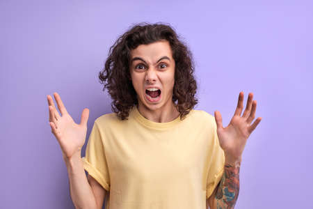 Nervous irritated curly man scream at camera spreading arms, feeling stress, worried about something, stand with wide opened mouth isolated over purple background Standard-Bild