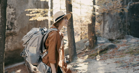Young traveler female in a broad-brimmed hat and backpack admires the forest, looks around