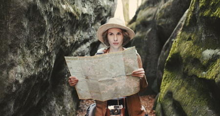 Stylish young traveler girl in hat looking at map, exploring woods Banco de Imagens