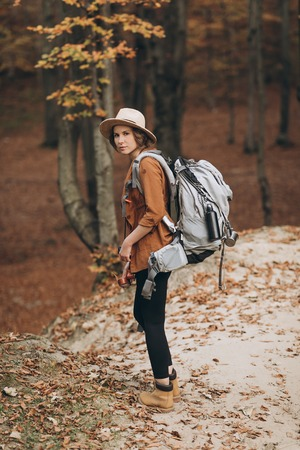 woman traveler with backpack looking at amazing forest, travel concept, space for text, atmospheric epic moment