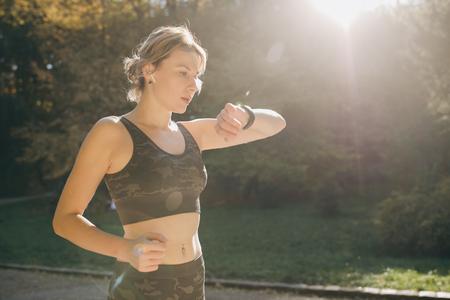 Fitness Woman In Wireless Earphones Using Smartwatch and runs in morning light Standard-Bild