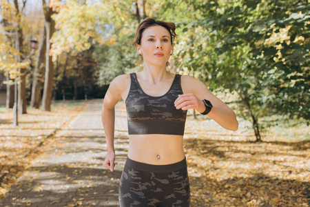 Female athlete woman runner wearing wireless earphones listening to music on smart phone