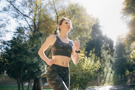Portrait of attractive brunette female runner running in city park airpods bluetooth headphones earphones. Healthy fitness athletic woman jogging outdoors Reklamní fotografie