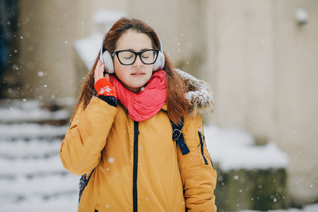 Attractive young girl Going the city and listening to music on the phone. Stylish look, casual accessories. Trendy look