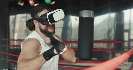 Muscular boxer man with vr glasses fighting in simulated virtual reality