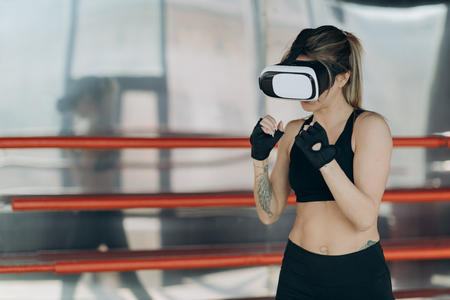 Attractive woman boxing in VR 360 headset training for kicking in virtual reality Stock Photo