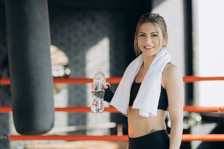 Attractive sport girl smiling and drinking water while standing in fitness class