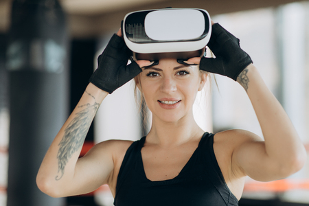 Young teen gamer wearing augmented reality glasses standing in boxing stance playing action simulator game mobile app