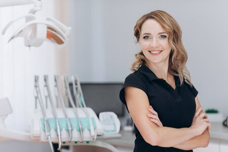 Female dentist standing in his office and looking at camera