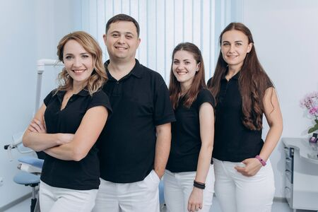 Group of dentists standing in their office and looking at camera