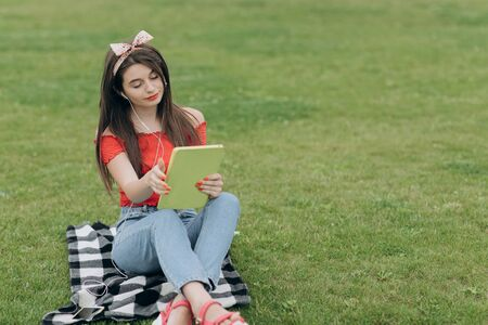 Woman listening music through headset and reading book in park