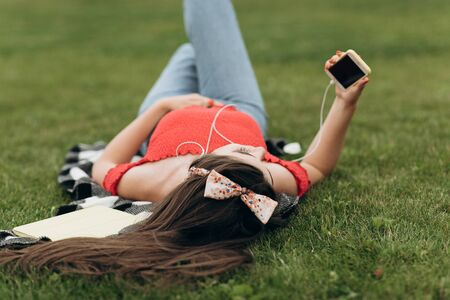 Girl resting on grass and listening to music