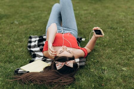 Woman listening to the music. Girl resting on grass and listening to music