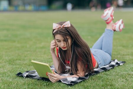 Girl resting on grass. Summer day. Young smiling woman in sunglasses lying on green lawn. Girl listens to music on headphones with your smartphone, uses gadget.