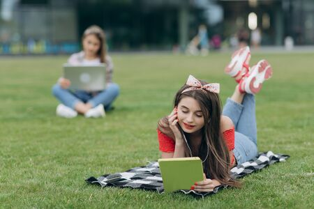 Girl reading book in park, sitting on grass and having rest in university campus. Woman listening music through headset and reading book in park