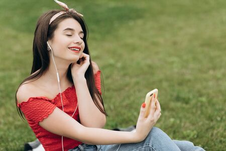 Portrait of content young beautiful woman wearing headphones, listening to music with her eyes closed and lying on grass in park