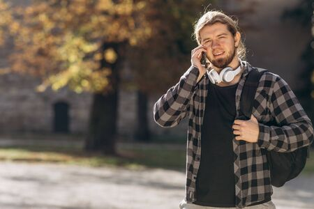 Trendy man in town using smartphone. Happy guy walking and using a smart phone to listen music with headphones. Happy hipster man walking in autumn park and smiling. Short haited man looking at camera