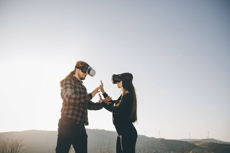 Two people wearing VR glasses. Young adult Caucasian male and female using holographic augmented reality glasses together.