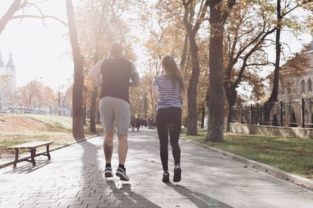 Young guy and girl working out. Fitness couple running together on sunny park. Man and woman at sport training together. Athletic newlyweds exercising together. Sport couple run together in park.