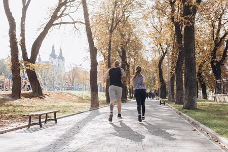 Back view of Fitness couple running together on sunny park. Athletic newlyweds exercising together. Young guy and girl working out. Sport couple run together in park. Man and woman training together Stock Photo