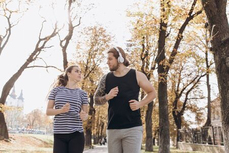 Man and woman at sport training together. Young people jogging together at fitness training outdoor. Sport couple run together in park.
