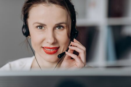 Young female customer service agent talking to a customer with a telephony headset as she looks at the camera.
