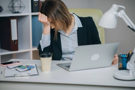 Tired Woman in Glasses Sitting at the Laptop Computer while Working in the Office, then Almost Falling Asleep and Waking Up