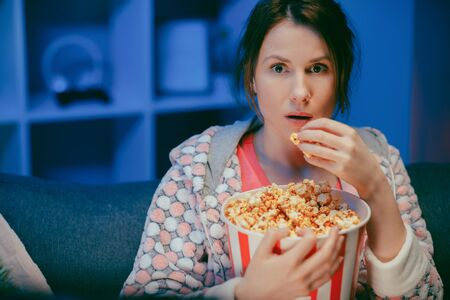 Portrait shot of the woman with popcorn sitting on the sofa watching something scary while eating popcorn and being afraid Stock Photo