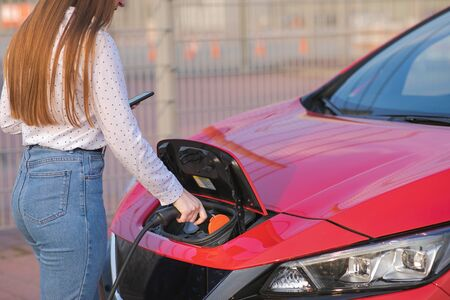 Woman Hand Attaching Power Cable To Environmentally Friendly Zero Emission Electric Car. Woman makes power supply plugged into an electric car being charged.