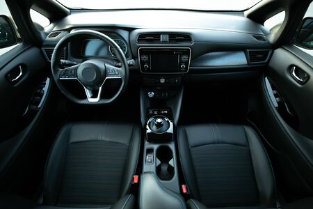 Electric car interior details of door handle with windows controls and adjustments. Inside car interior with front seats, driver and passenger, textile, windows, door panels, console Foto de archivo