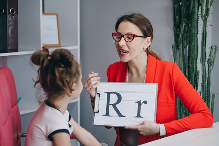 Voice Ability Problem Speaking Lesson Concept. Speech therapist teaches the girls to say the letter R. Female Speech Language Therapist Teaching Preschool Kid Sound Pronunciation