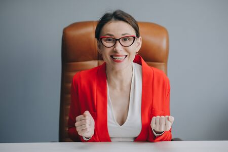 Cute girl holding her glasses and smiling. Beautiful happy businesswoman working at home office Banque d'images