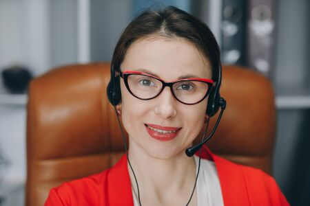 Video chat job interview or distance language course class with online teacher concept. Happy young woman wear headset communicating by conference call speak looking at computer at home office