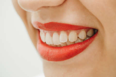 Beautiful toothy smile. Close up portrait of beautiful young happy smiling woman, isolated over white background. Laughing woman smile with great teeth.