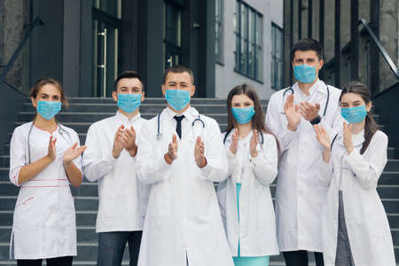 Corona Virus and Healthcare Concept. Medical staff from the hospital who are fighting coronavirus applaud back the people for their support. Group of doctors with face masks looking at camera