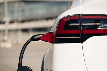 Electric vehicle charging port plugging in EV modern car. Save ecology alternative energy sustainable of future. Plug charging an electrical car.