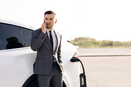 Portrait of handsome joyful 30-aged businessman with neat beard which has mobile conversation while own luxurious car charging battery on specially-equipped charging station