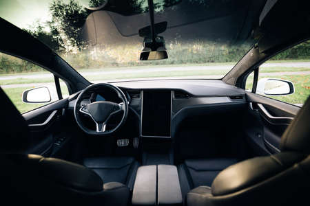 Electric car interior details of door handle with windows controls and adjustments. Inside car interior with front seats, driver and passenger, textile, windows, door panels, console