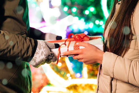 Gift Box. Boyfriend Making Holiday Surprise to His Woman Celebrating Together Giving Christmas Present. Happy Couple Stand Outdoors
