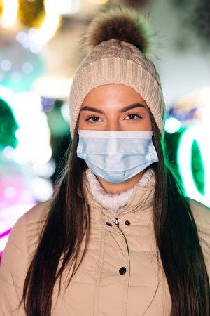 Close up portrait of Caucasian female in medical face mask standing in decorated xmas city. Crowd people sick covid-19. Epidemic coronavirus. Pandemic flu corona virus.