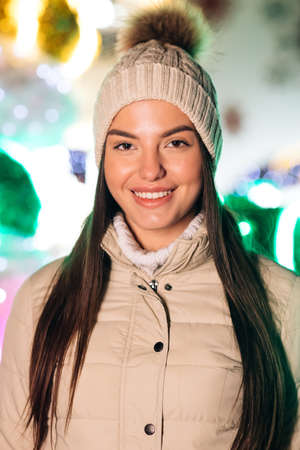 Portrait of joyful caucasian woman in hat looking at camera smiling around Christmas lights in city center. Positive mood happy emotion standing outdoor. Winter beautiful street face outdoor