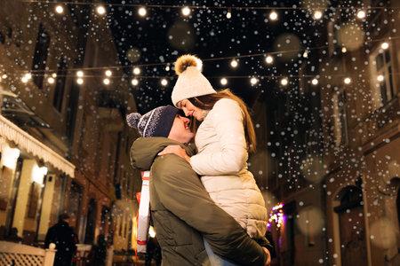 Christmas gifts exchange. Xmas celebration together. Smiling couple celebrating Xmas eve together at bright garland decoration. Фото со стока
