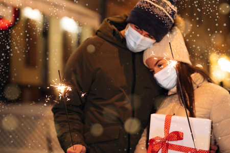 Unrecognizable Couple Hands holding and waving sparklers. Party on occasion of New Year, Christmas Eve or Xmas. Lifestyle. Couple in protective medical masks standing on the street holding sparklers Фото со стока