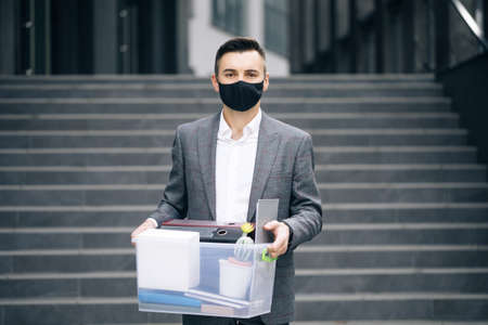 Fired sad young businessman in medical mask carries box with personal belongings leaving the office. Unemployment. Lack of jobs. Financial crisis. Фото со стока