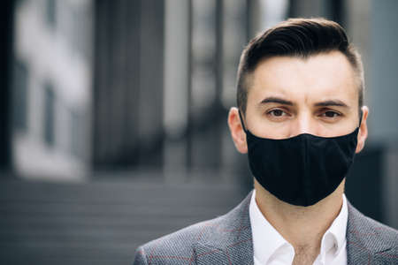 Portrait of an caucasian man out and about in the city streets during the day, wearing a face mask against air pollution and covid19 coronavirus
