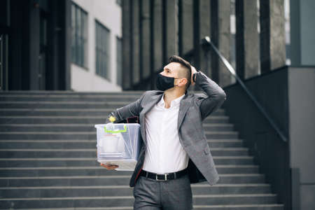 Sad male office worker in depression with box of personal stuff. Businessman lost job. Fired man walking outdoor. Depressed jobless person. Unemployment concept. Left without money.
