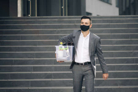 Fired man walking outdoor. Depressed jobless person. Unemployment concept. Left without money. Sad male office worker in depression with box of personal stuff. Businessman lost job Фото со стока